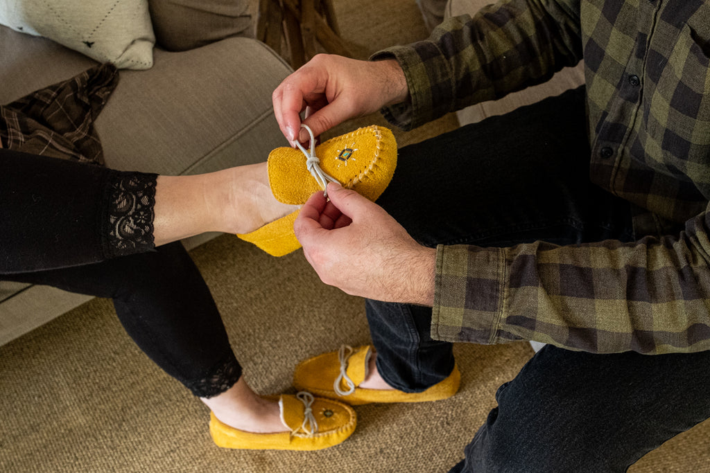 men tying womens shoe lace on authentic moccasins