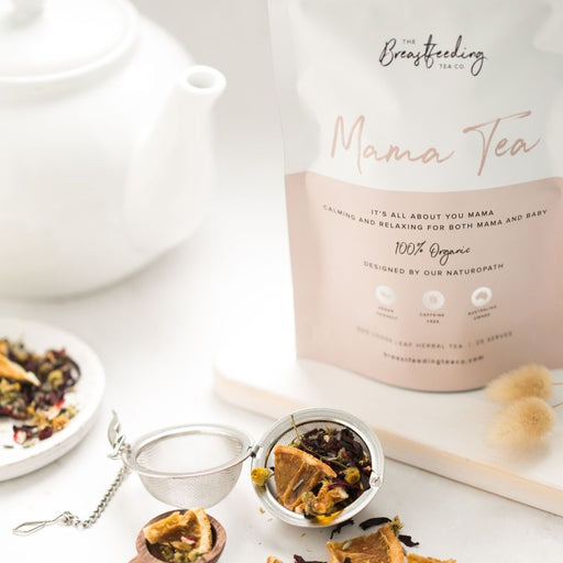 A packet of Mama Tea by Breastfeeding Tea Co arranged with a white teapot and metal tea strainer