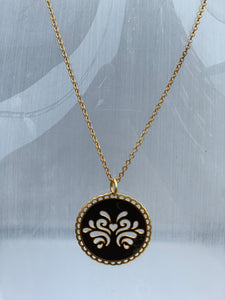 Circular reversible pendant on a chain