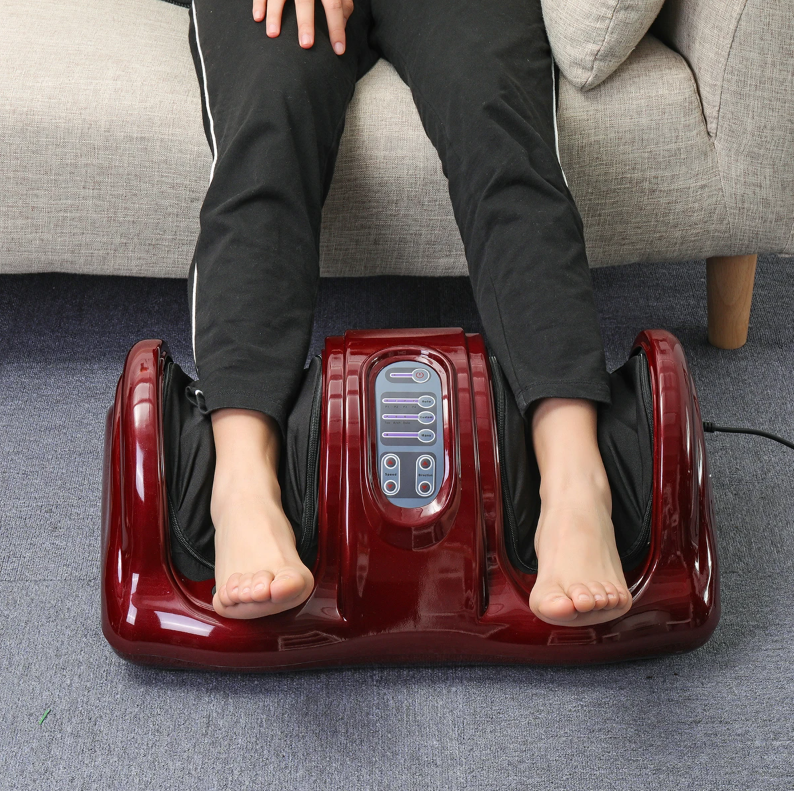 womens legs in black track pants using the red leg and foot massager