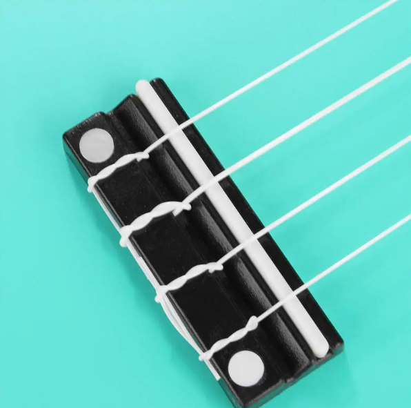 close up of white strings tied to bridge of spearmint color ukulele