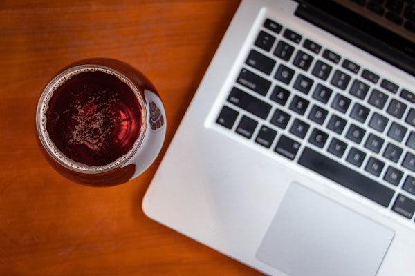 Glass of red wine adjacent to laptop computer