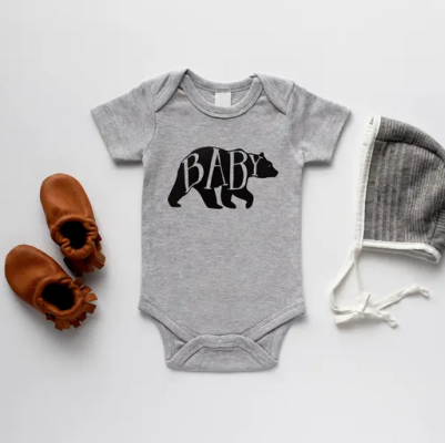 "Short Sleeved Grey baby onesie with black grizzly bear outline containing the word ""Baby"", pictured with a gray bonnet and booties"