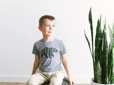 A boy wearing a Brother bear tshirt, sitting next to a plant