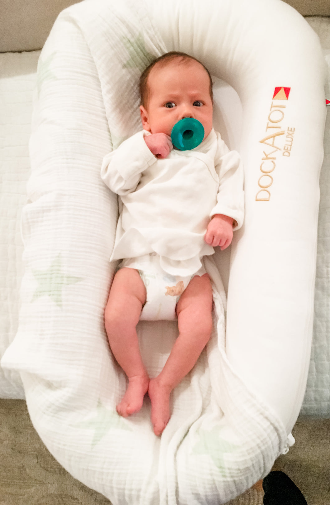 Baby with pacifier in DockATot Deluxe lounger