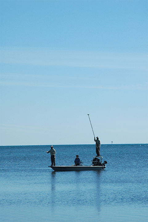 Distant view of three anglers on boat in water