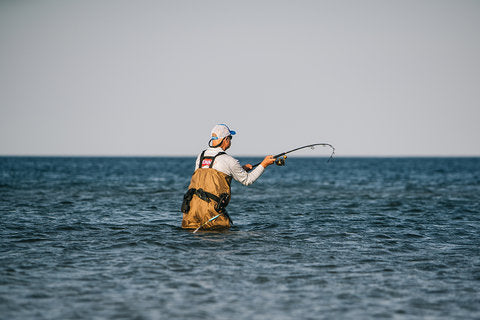 Angler wading in ocean casting line