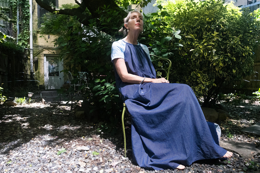 Susannah Thompson sitting in a garden wearing the M.PATMOS Laia Dress in Navy Stripe