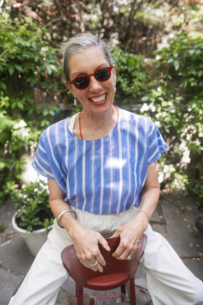 Susannah Thompson sitting in a garden wearing the M.PATMOS Milton Top and Elsa Pants