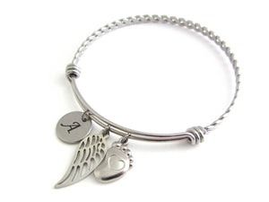 stainless steel laser engraved capital initial letter disc charm, a single angel wing charm and a single foot charm with indented heart on a bangle with braided twist pattern