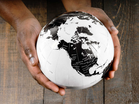 white and black world globe held in hands
