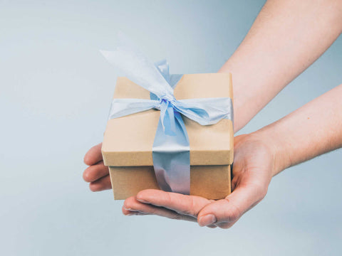 hands holding gift box tied with a blue ribbon