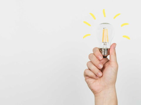 hand holding lightbulb with bright idea lines