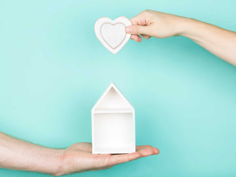 hands holding wooden heart over small house