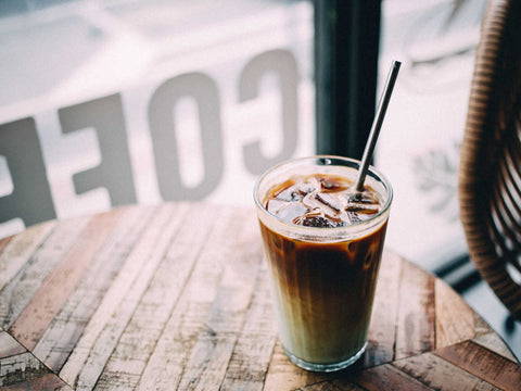 iced latte on table by coffee shop window
