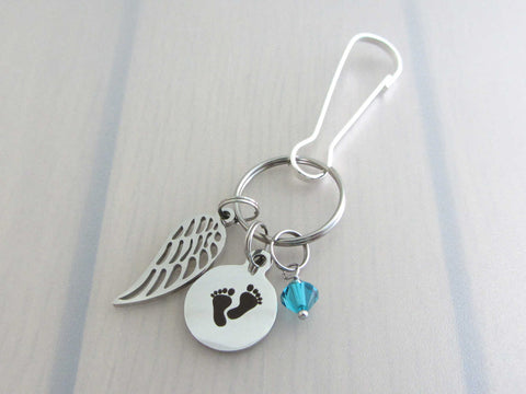 stainless steel single angel wing charm, a laser engraved baby footprints charm and a blue/green coloured crystal charm on a bag charm with snap clip hook
