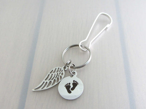 stainless steel single angel wing charm and a laser engraved baby footprints charm on a bag charm with snap clip hook