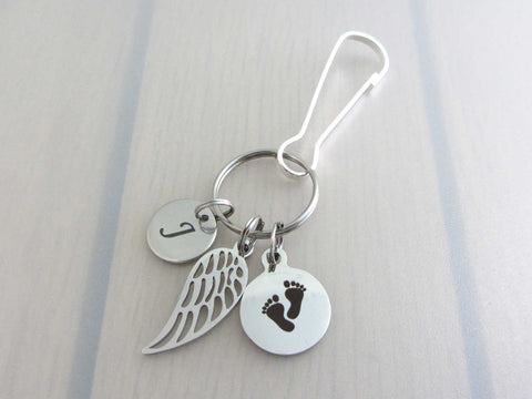 stainless steel laser engraved capital initial letter disc charm, a single angel wing and a laser engraved baby footprints charm on a bag charm with snap clip hook