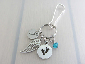 stainless steel laser engraved capital initial letter disc charm, a single angel wing charm, a laser engraved baby footprints charm and a blue/green coloured crystal charm on a bag charm with snap clip hook