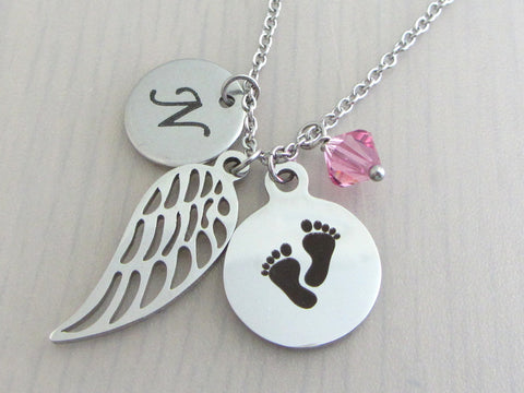 laser engraved capital initial letter disc charm, a single angel wing charm, a laser engraved baby footprints charm and a pink crystal charm on a stainless steel chain