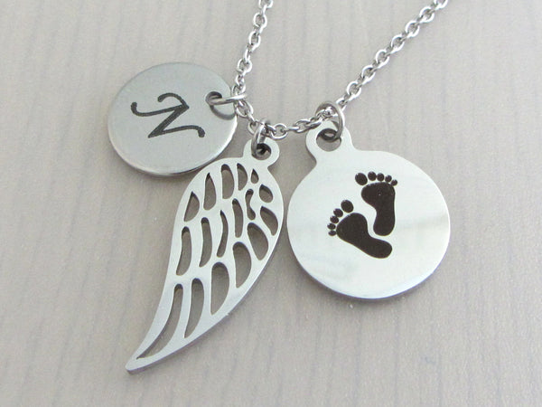 laser engraved capital initial letter disc charm, a single angel wing charm and a laser engraved baby footprints charm on a stainless steel chain