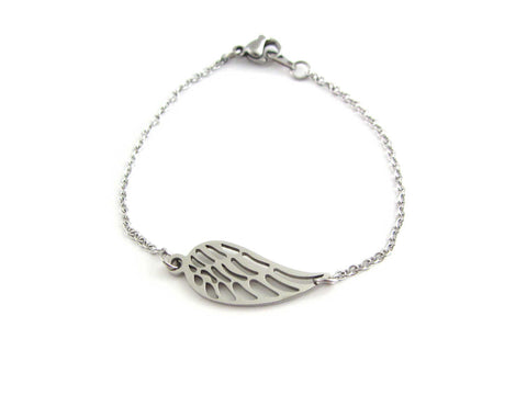 single angel wing charm on a stainless steel chain bracelet on wrist