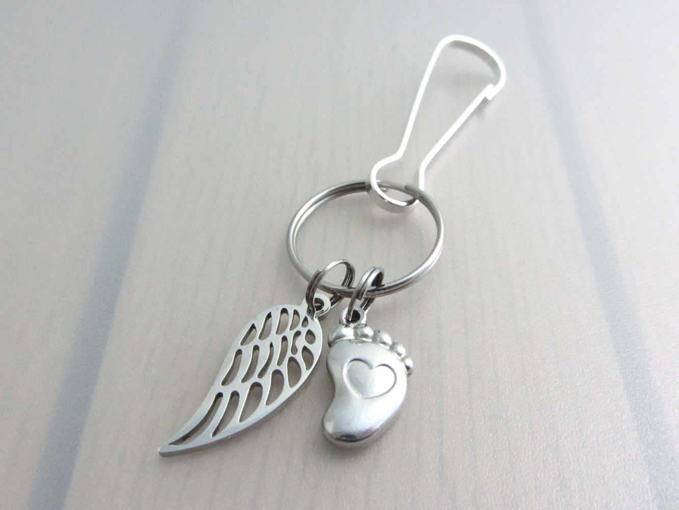 stainless steel single angel wing charm and a single foot charm with indented heart on a bag charm with snap clip hook