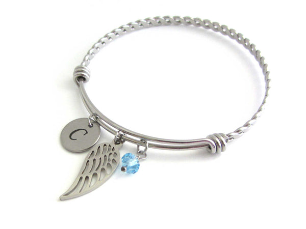 stainless steel laser engraved capital initial letter disc charm, single angel wing charm and a light blue crystal charm on a bangle with braided twist pattern