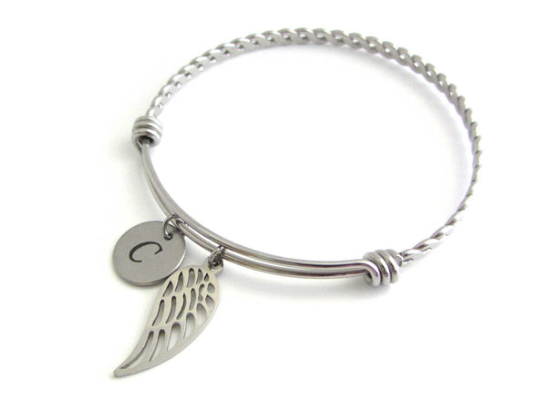 stainless steel laser engraved capital initial letter disc charm and single angel wing charm on a bangle with braided twist pattern