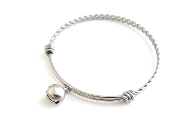 stainless steel bell charm on a bangle with braided twist pattern