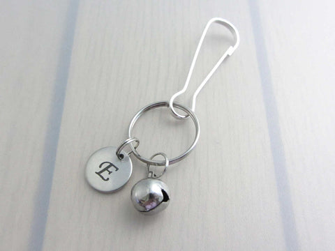 stainless steel laser engraved capital initial letter disc charm and bell charm on a bag charm with snap clip hook