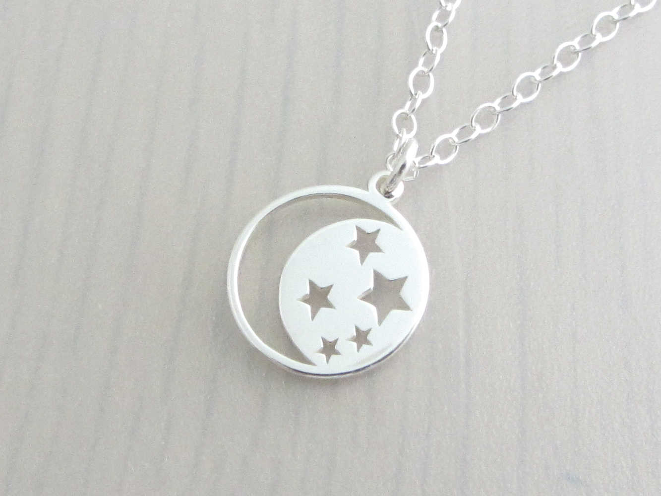 silver crescent moon with cut out stars charm on a silver chain