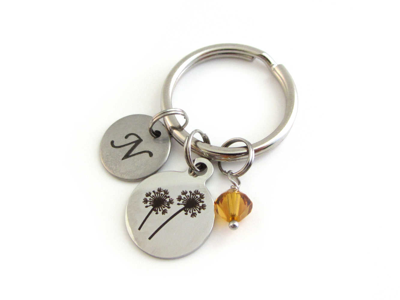 laser engraved capital initial letter disc charm, a laser engraved dandelion flowers charm and an orange crystal charm on a keyring
