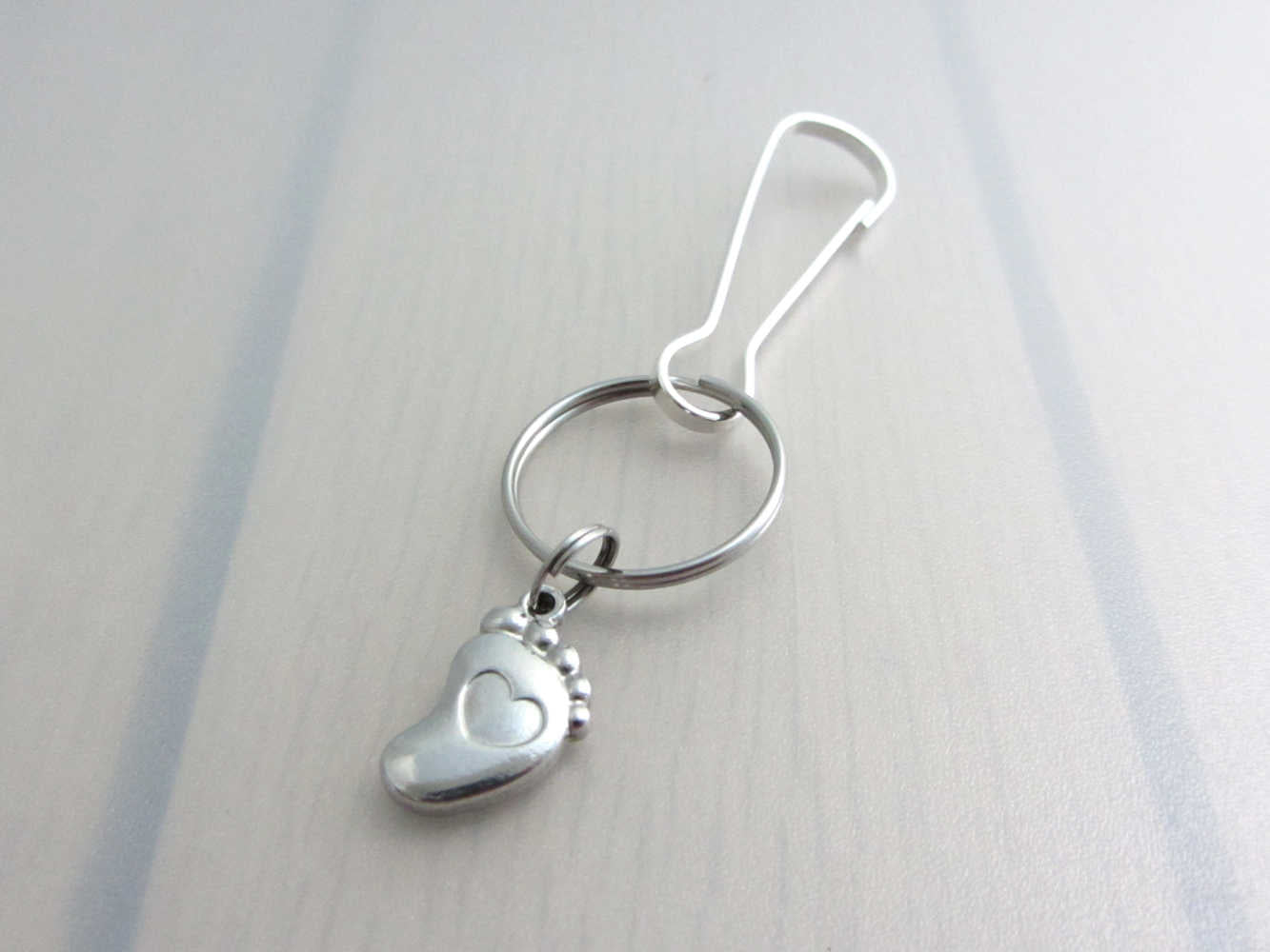 stainless steel single foot charm with indented heart on a bag charm with snap clip hook