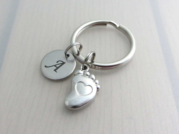 stainless steel laser engraved capital initial letter disc charm and a single foot charm with indented heart on a keyring