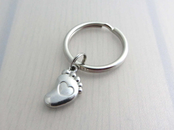 stainless steel single foot charm with indented heart on a keyring