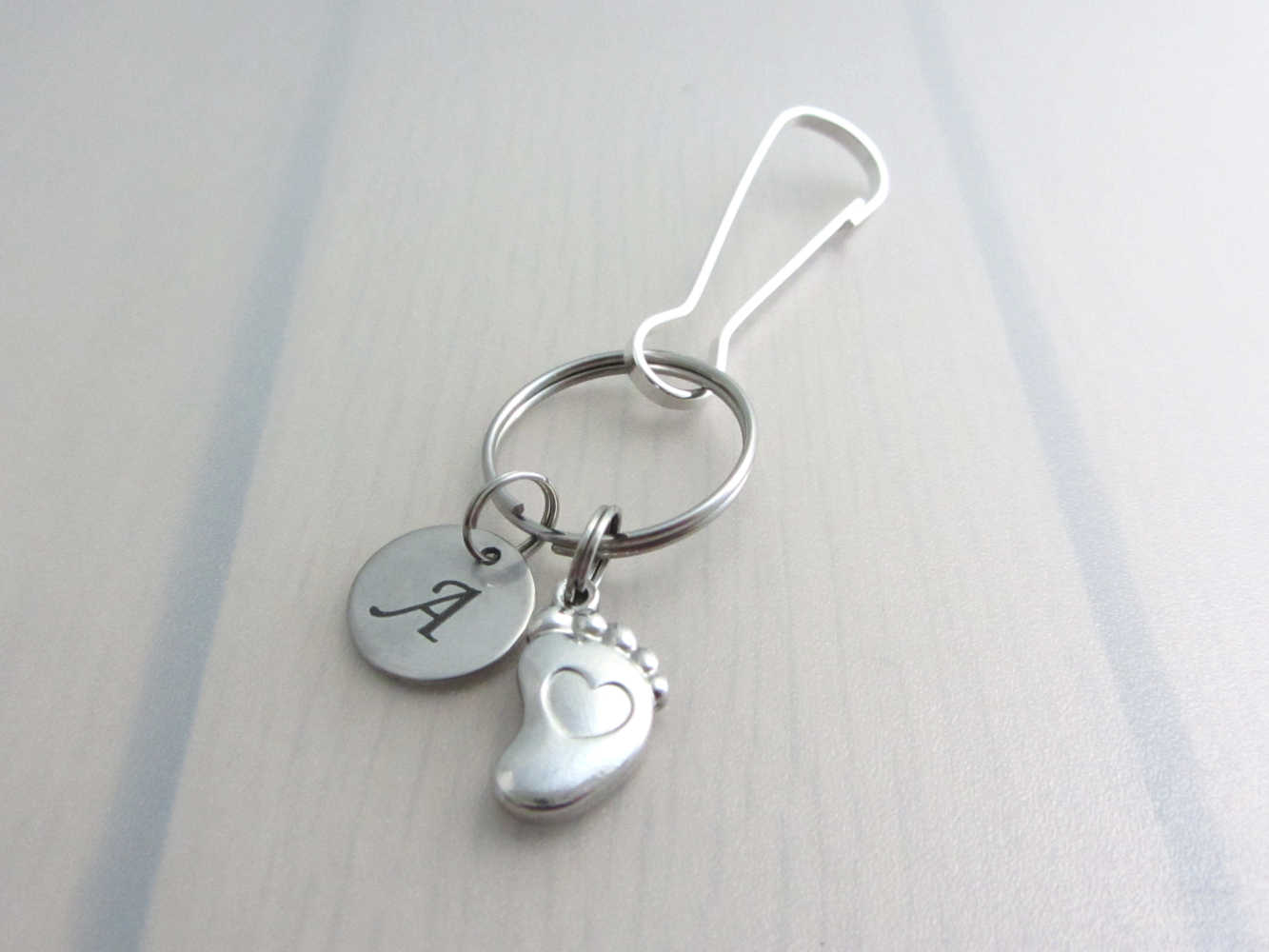 stainless steel laser engraved capital initial letter disc charm and a single foot charm with indented heart on a bag charm with snap clip hook