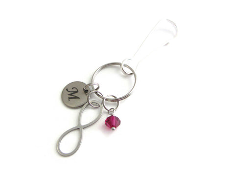 stainless steel laser engraved capital initial letter disc charm, an infinity charm and a red crystal charm on a bag charm with snap clip hook