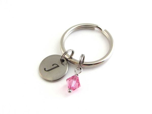 stainless steel laser engraved capital initial letter disc charm and a pink crystal charm on a keyring