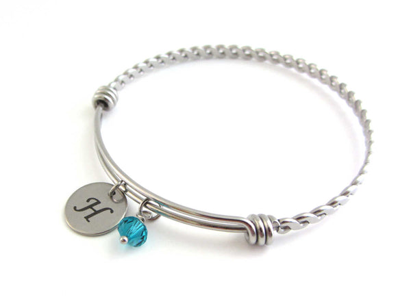 laser engraved capital initial letter disc charm and a blue green crystal charm on a bangle with braided twist pattern