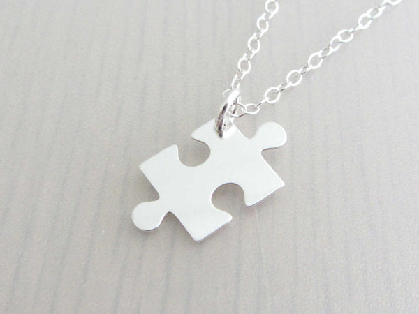 silver jigsaw puzzle piece charm on a silver chain