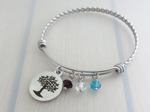 stainless steel laser engraved tree charm with coloured crystals on a bangle with braided twist pattern