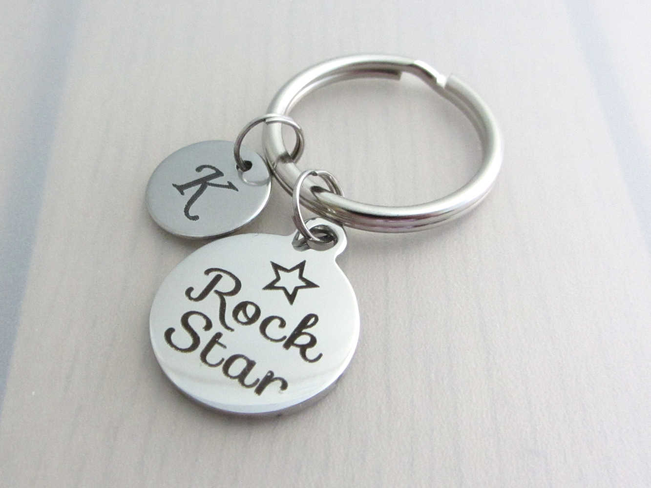 "stainless steel laser engraved capital initial letter disc charm and laser engraved ""rock star"" with star charm on a keyring"