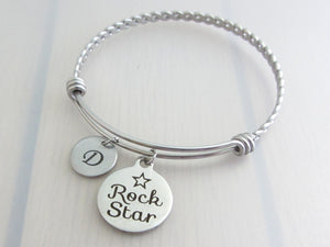 "stainless steel laser engraved ""rock star"" with star charm and capital initial letter disc charm on a bangle with braided twist pattern"