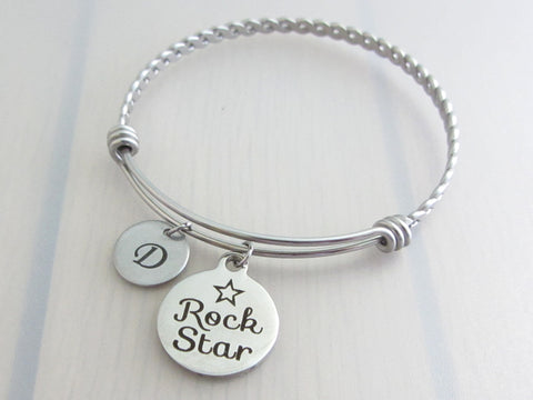 "stainless steel laser engraved ""rock star"" with star disc charm and capital initial letter disc charm on a bangle with braided twist pattern"