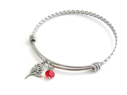 rose flower charm and a red crystal charm on a bangle with braided twist pattern