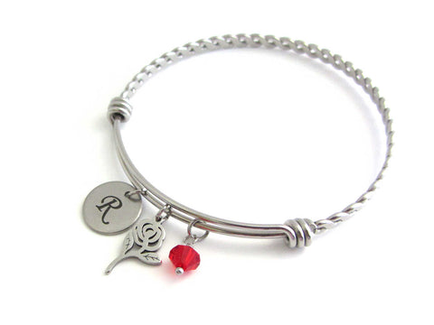 laser engraved capital initial letter disc charm, rose flower charm and a red crystal charm on a bangle with braided twist pattern