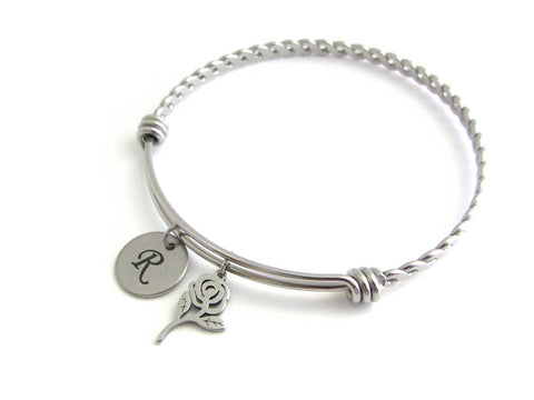 laser engraved capital initial letter disc charm and a rose flower charm on a bangle with braided twist pattern