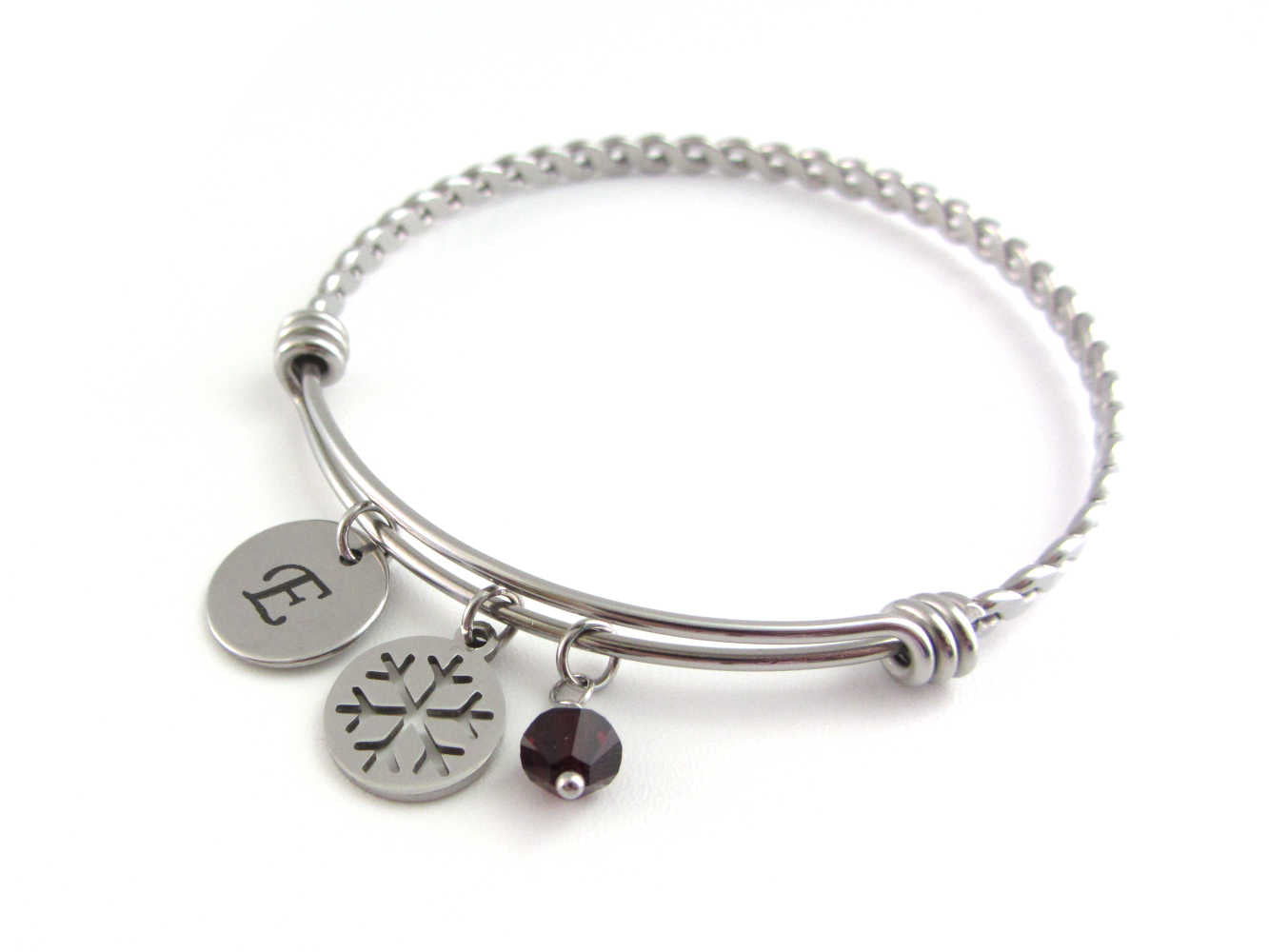 laser engraved capital initial letter disc charm, snowflake charm and a red crystal charm on a bangle with braided twist pattern