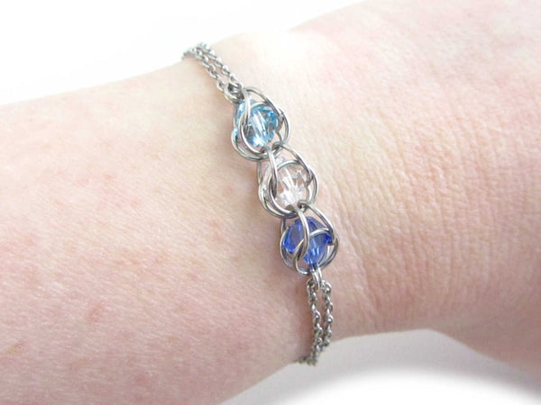 captured light blue, clear and dark blue crystal beads chainmaille bracelet on wrist
